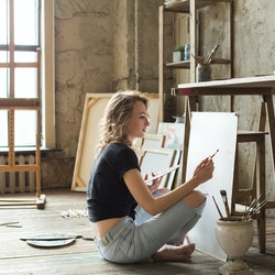 Woman painter sitting on the floor in front of the canvas and drawing. Artist studio interior. Drawing supplies, oil paints, artist brushes, canvas, frame. Workshop or art class. Creative concept