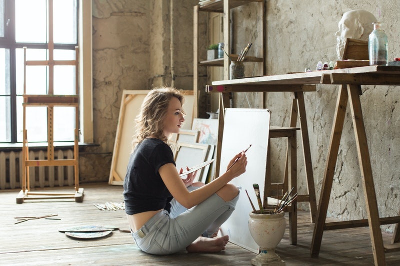 Woman painter sitting on the floor in front of the canvas and drawing. Artist studio interior. Drawi...