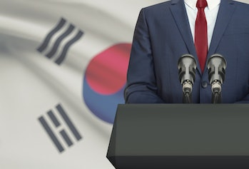 Businessman or politician making speech from behind the pulpit with national flag on background - South Korea