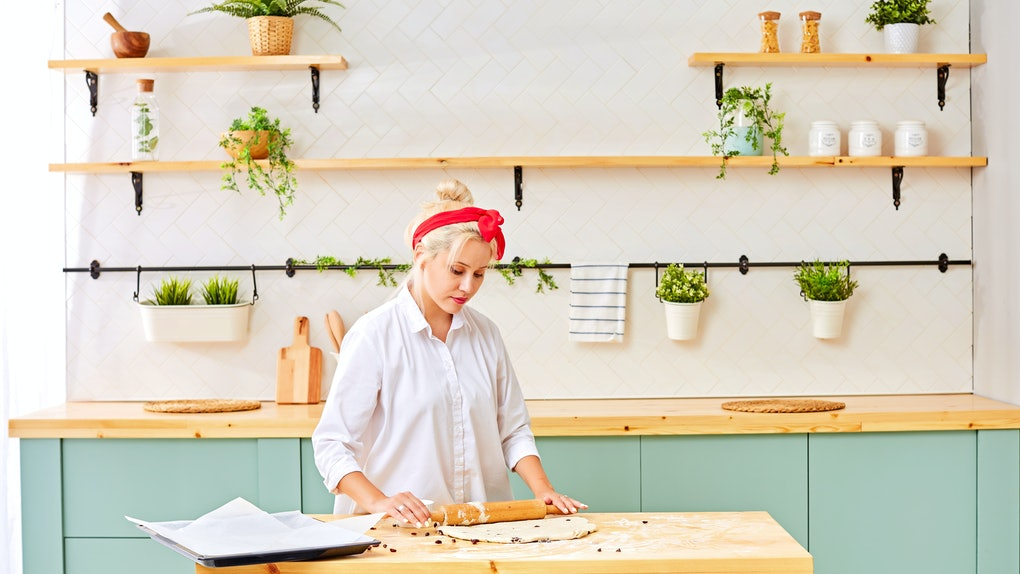 A blonde woman with a red headband and white button-down shirt rolls out dough in her bright kitchen.