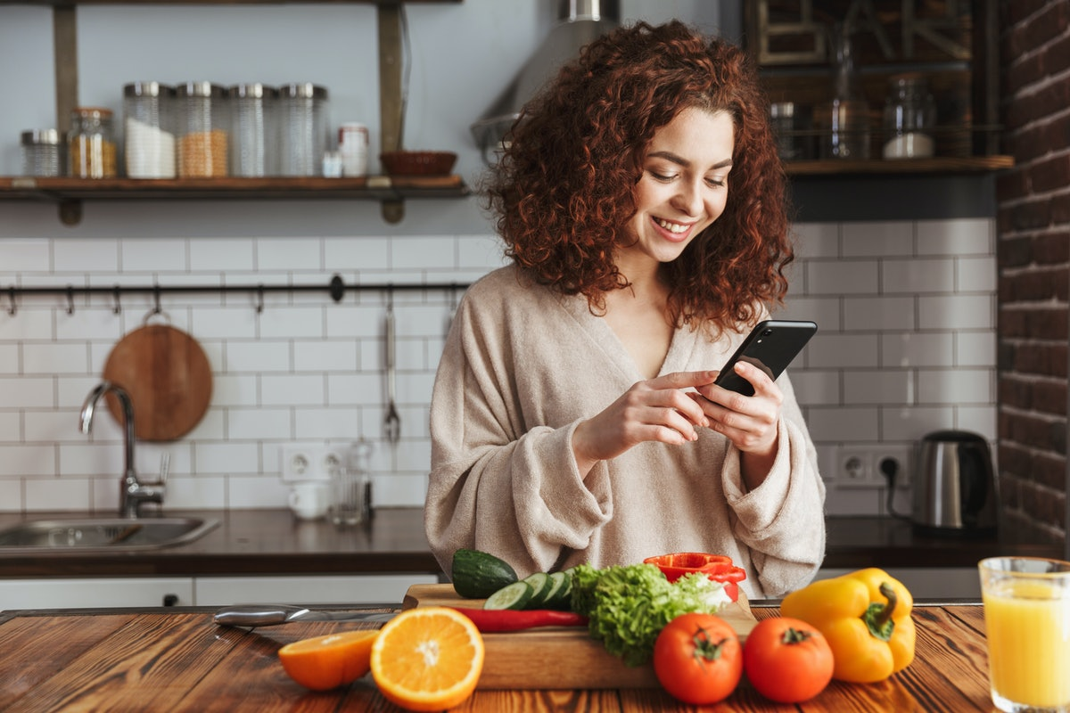 A happy woman looks at her phone, while standing in her kitchen with vegetables in front of her.