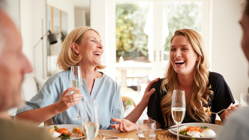 A happy and laughing mother and daughter enjoy brunch together at home.