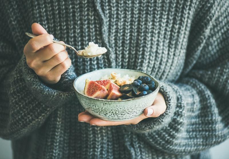 Healthy winter breakfast. Woman in woolen sweater eating rice coconut porridge with figs, berries, h...
