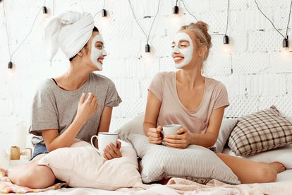 Portrait of pretty joyful friends doing beauty treatments at home. Cheerful young women relaxing in cozy bedroom and drinking coffee. Skincare concept