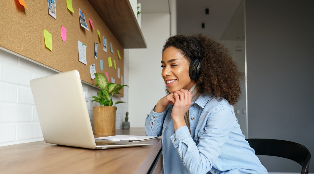 Smiling young african american teen girl wear headphones video calling on laptop. Happy mixed race pretty woman student looking at computer screen watching webinar or doing video chat by webcam.