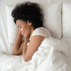 Serene calm african american woman sleeping in comfortable bed lying on soft pillow orthopedic mattress, peaceful young black lady resting covered with blanket on white sheets in bedroom, top view