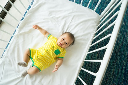 6 month old baby lying down in crib