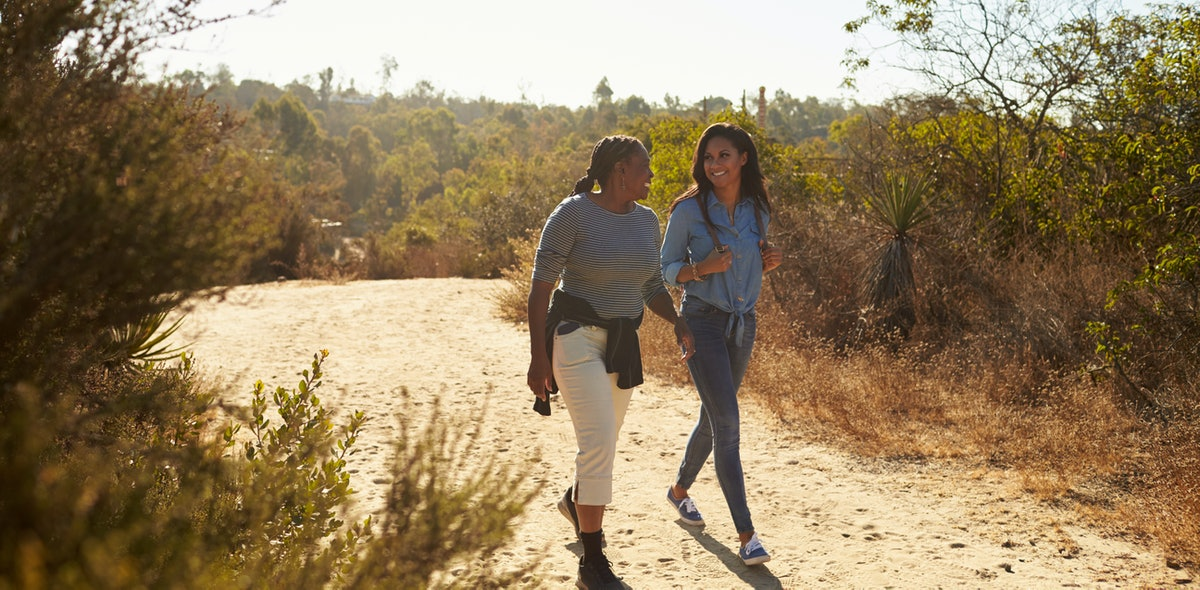A mother and daughter chat while hiking a dirt trail in the sunshine.