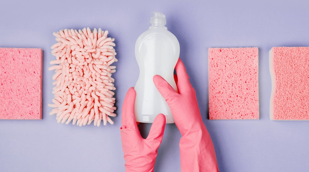 Detergents and cleaning accessories  in pink color.  Cleaning service concept. Flat lay, Top view.