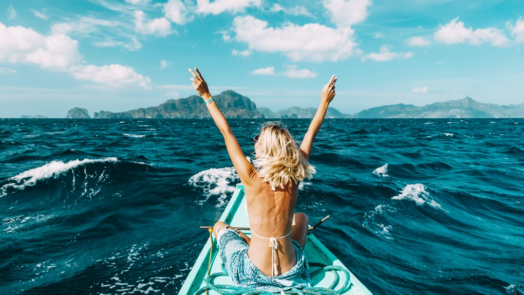 The back view of a blonde woman posing at the front of a blue boat, sitting cross-legged and holding up two peace signs.