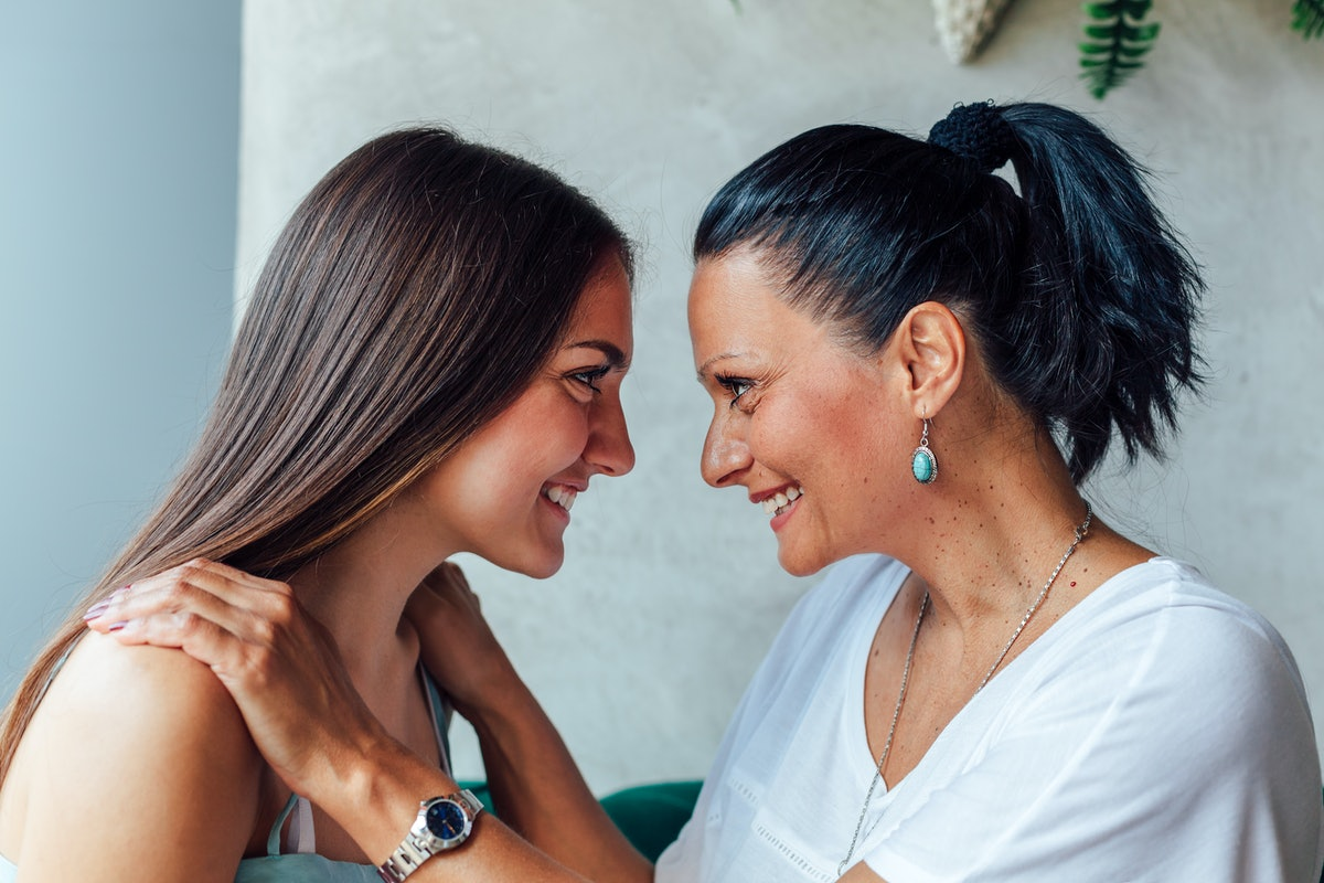 A mother and daughter smile and look at each other while chatting in a bright room.