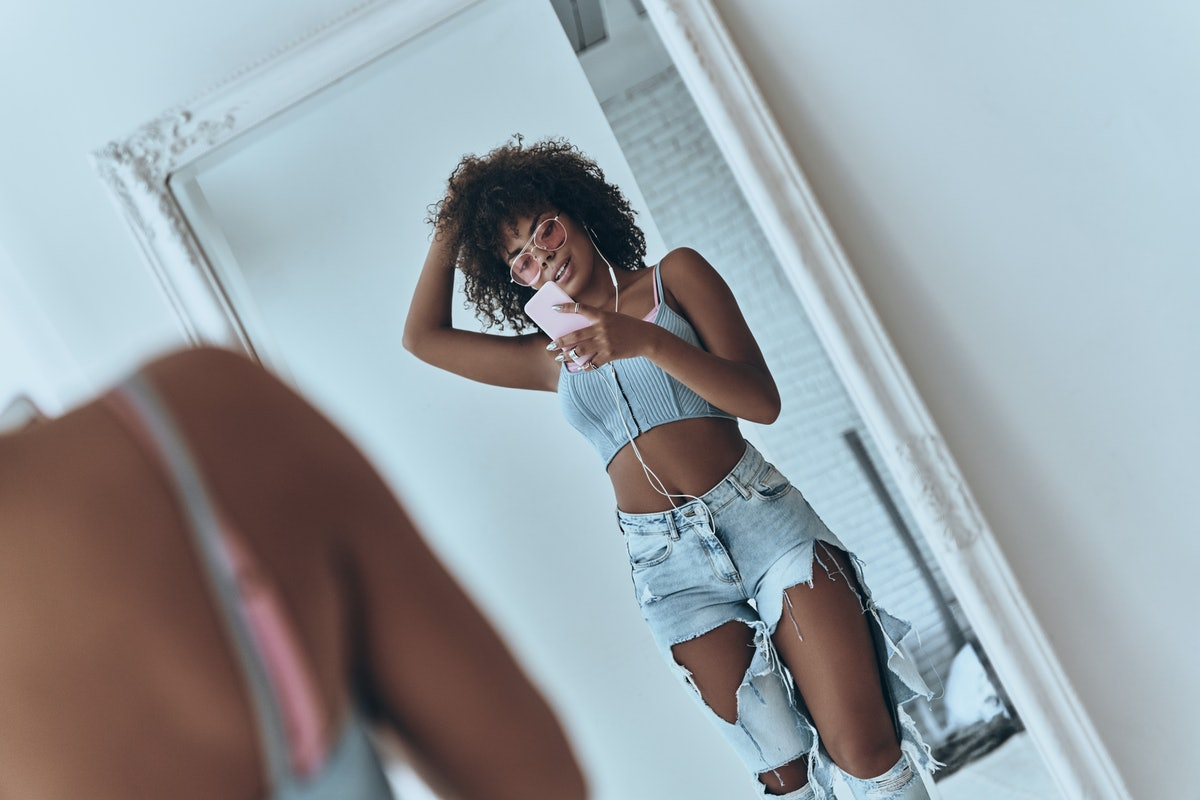 A woman wearing ripped jeans, a crop top, and pink sunglasses takes a mirror selfie in her room.
