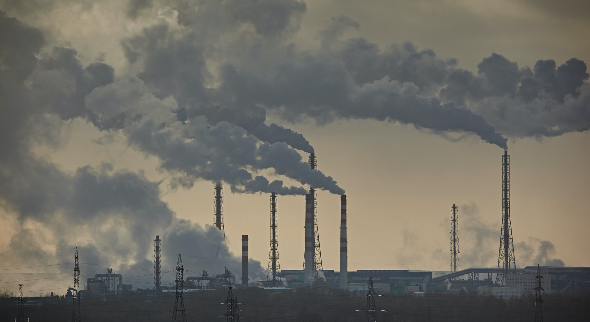 The plant emits smoke and smog from the pipes at mist cloudy, pollutants enter the atmosphere. Environmental disaster. Harmful emissions into. Exhaust gases. Chemical industry against the sky.