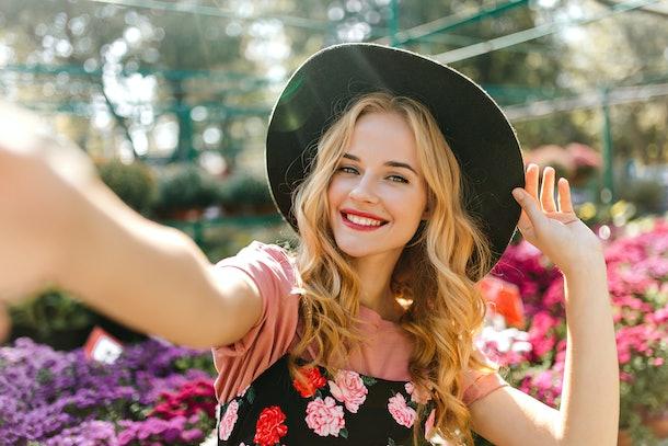 Stunning woman with beautiful eyes making selfie in orangery. Pleased girl in black hat posing with flowers