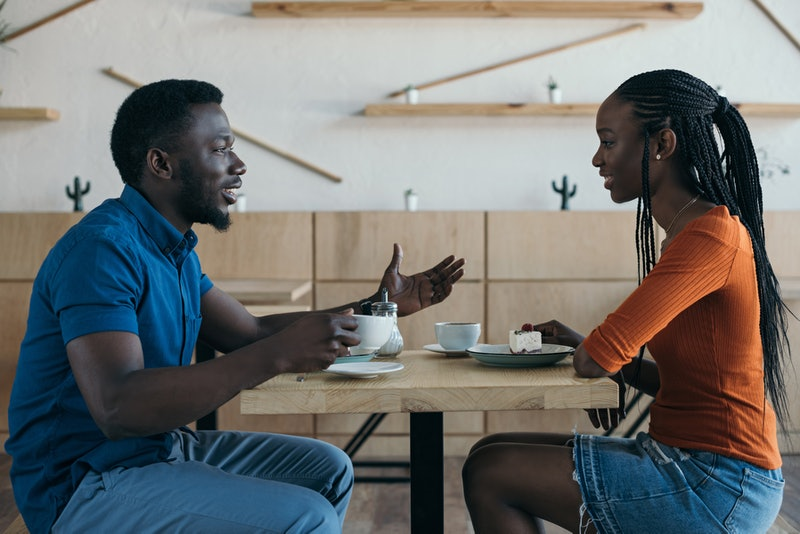 side view of african american couple having conversation during date in coffee shop