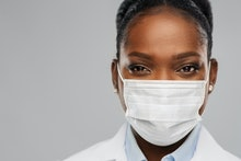 medicine, profession and healthcare concept - close up of african american female doctor or scientis...