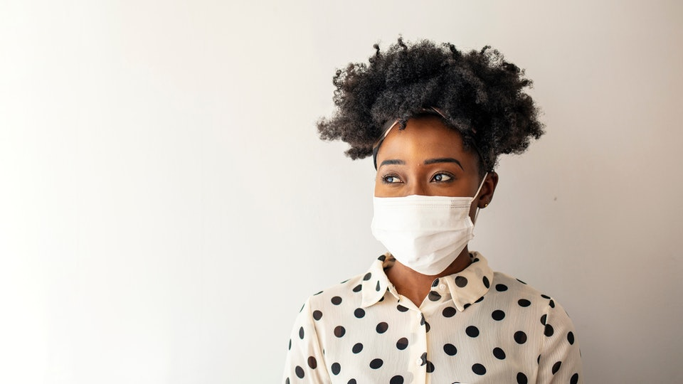 Masked woman - protection against influenza virus. African - American woman wearing mask for protect. Woman wear with protective face mask at home. Stop the virus and epidemic diseases.