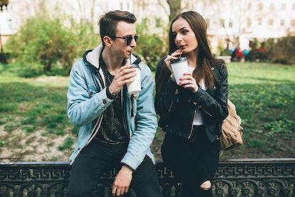 Stylish couple drinking coffee outdoors