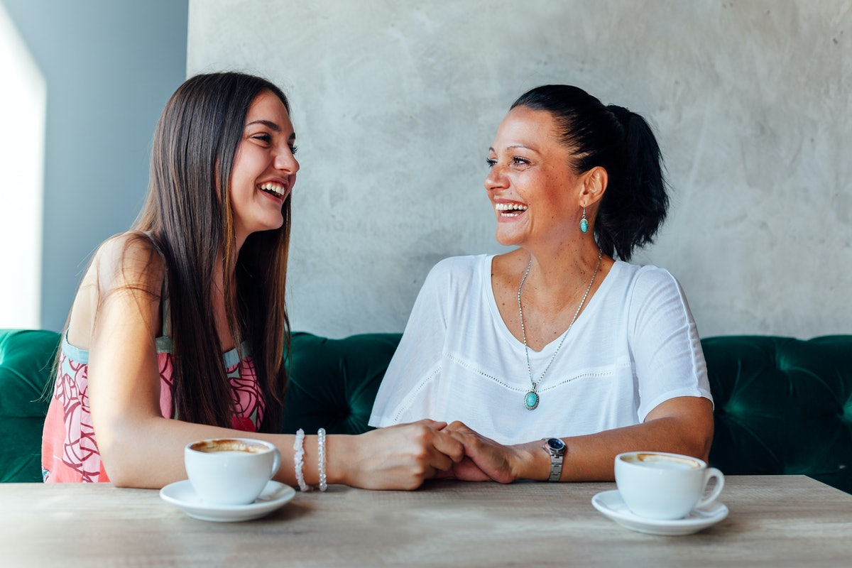 Mother and daughter smile and laugh in a café.