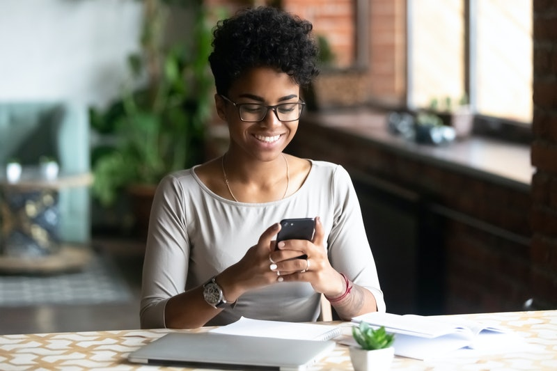 Cheerful african student black woman sitting at table studying using laptop reading a book, take a break holding mobile phone surfing internet received message from friend chatting about weekend plans