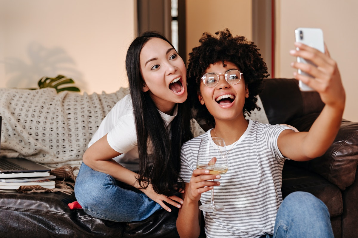 Two roommates smile for a selfie, while holding wine glasses on the couch.