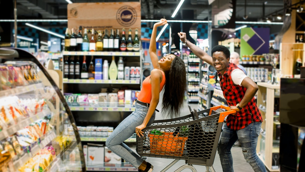 A happy couple dances in the aisle at the grocery store with their shopping cart.