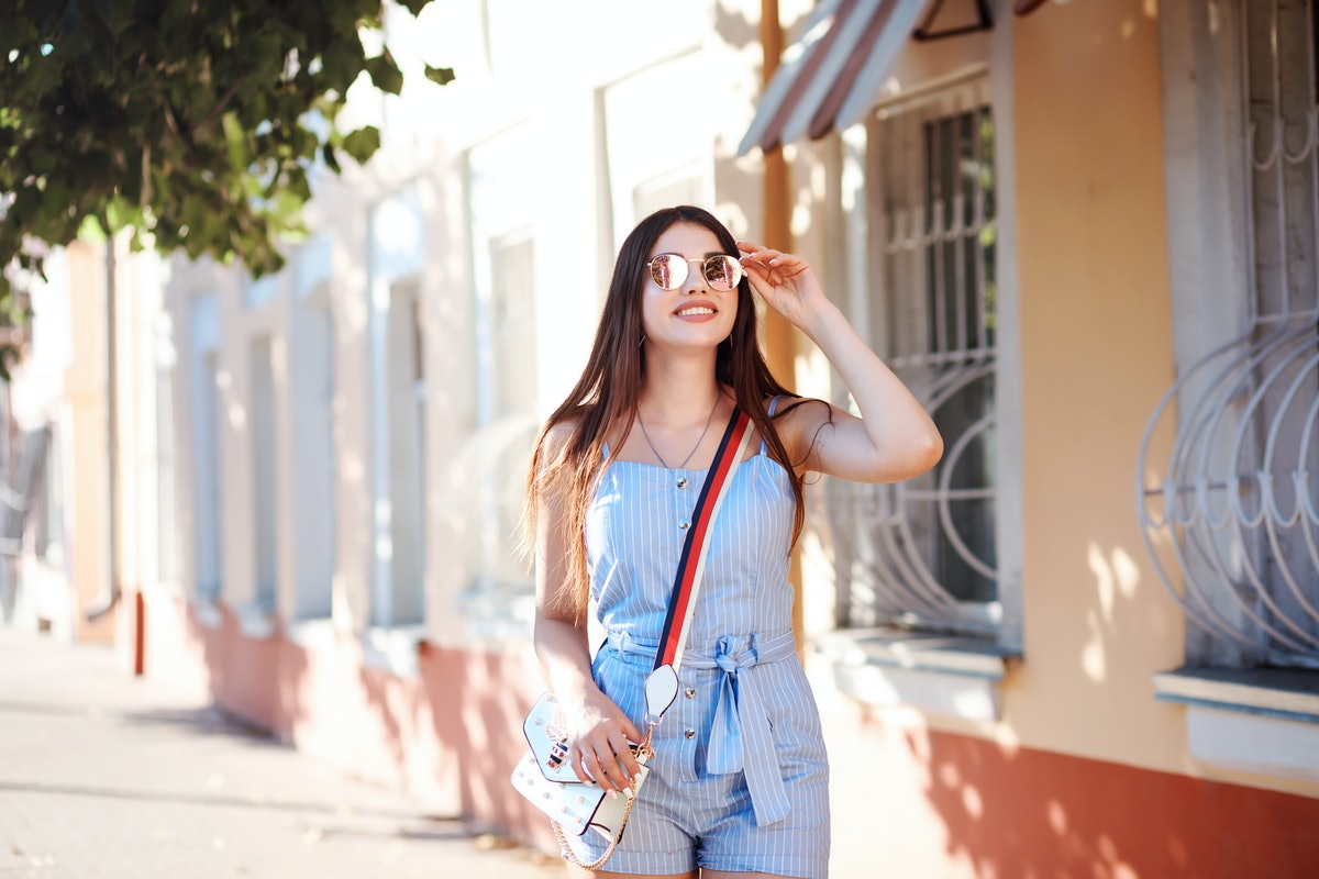 A woman in a blue romper and sunglasses walks down a sidewalk on a sunny afternoon.