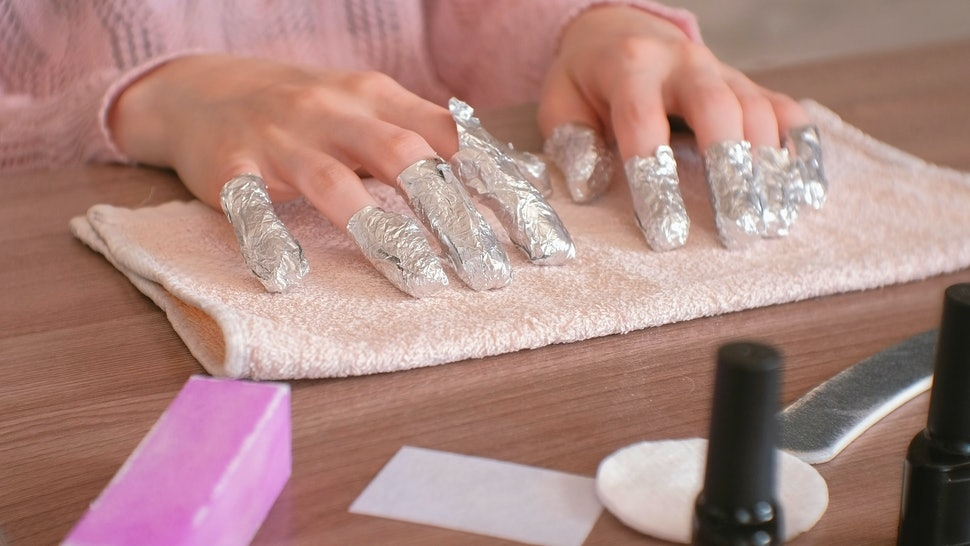 Removing gel Polish from nails. All fingers with foil on both hands. Close-up hand. Front view.