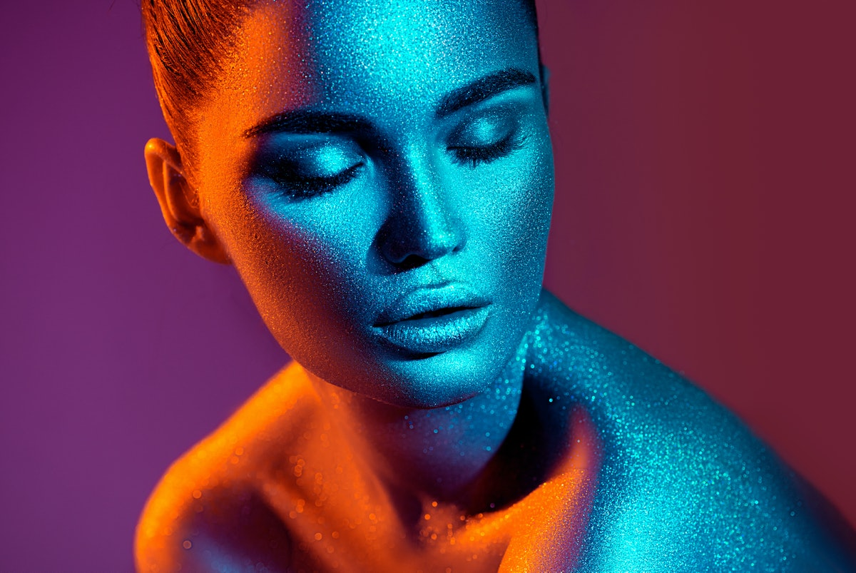 Young woman in neon lights with supernatural powers, according to her zodiac sign.
