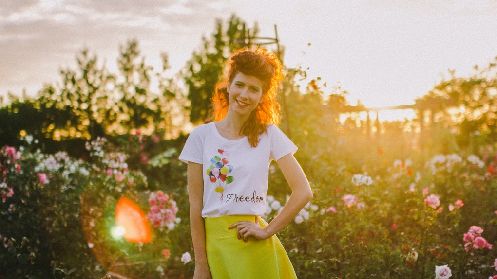 A redhead woman wears a yellow skirt and balloon shirt outside, next to some rose bushes.