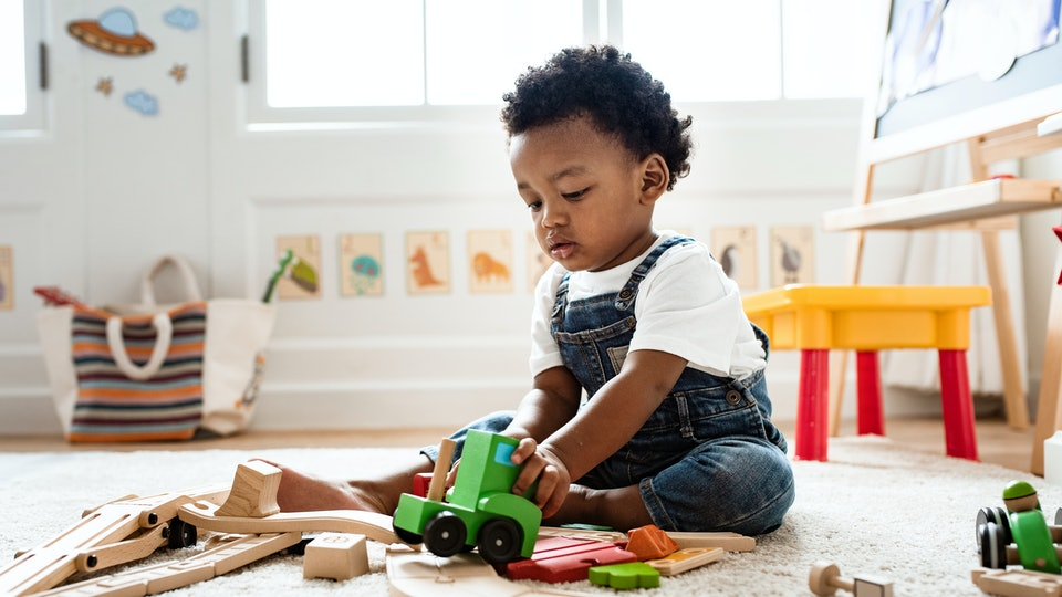 Cute little boy playing with a railroad train toy