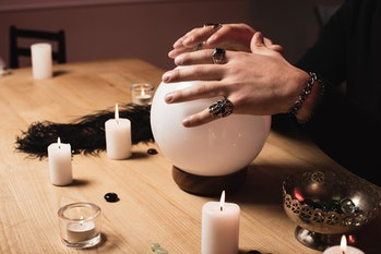 cropped view of psychic holding hands above magical crystal ball near candles