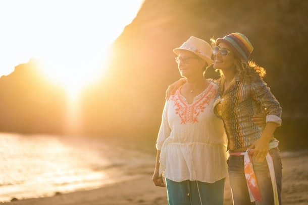 A mother and daughter smile and walk on a beach at sunset.
