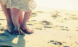 mother and baby feet in the sand on the beach