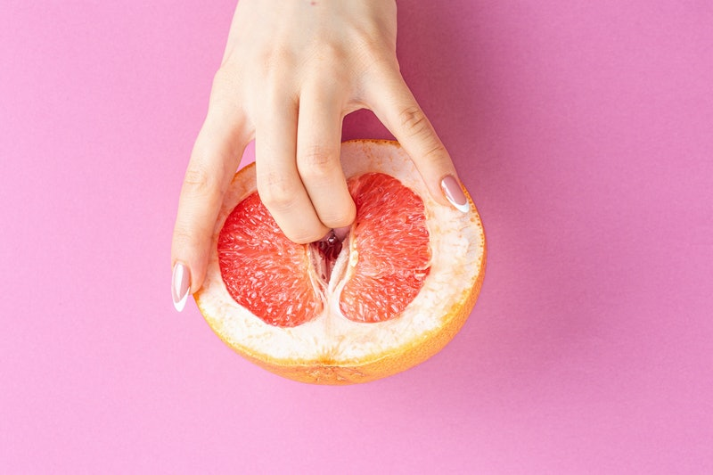 fingers in grapefruit on pink background. Sex and masturbation concept. sexy fruit composition. Vagi...