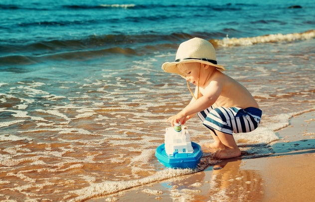 toddler boy playing with toy boat on the beach