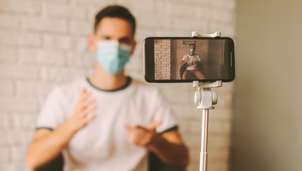 Handsome man recording video blog with instructions of preventive measures against coronavirus COVID-19. Young blogger in medical mask on face filming content for subscribers on smart phone camera