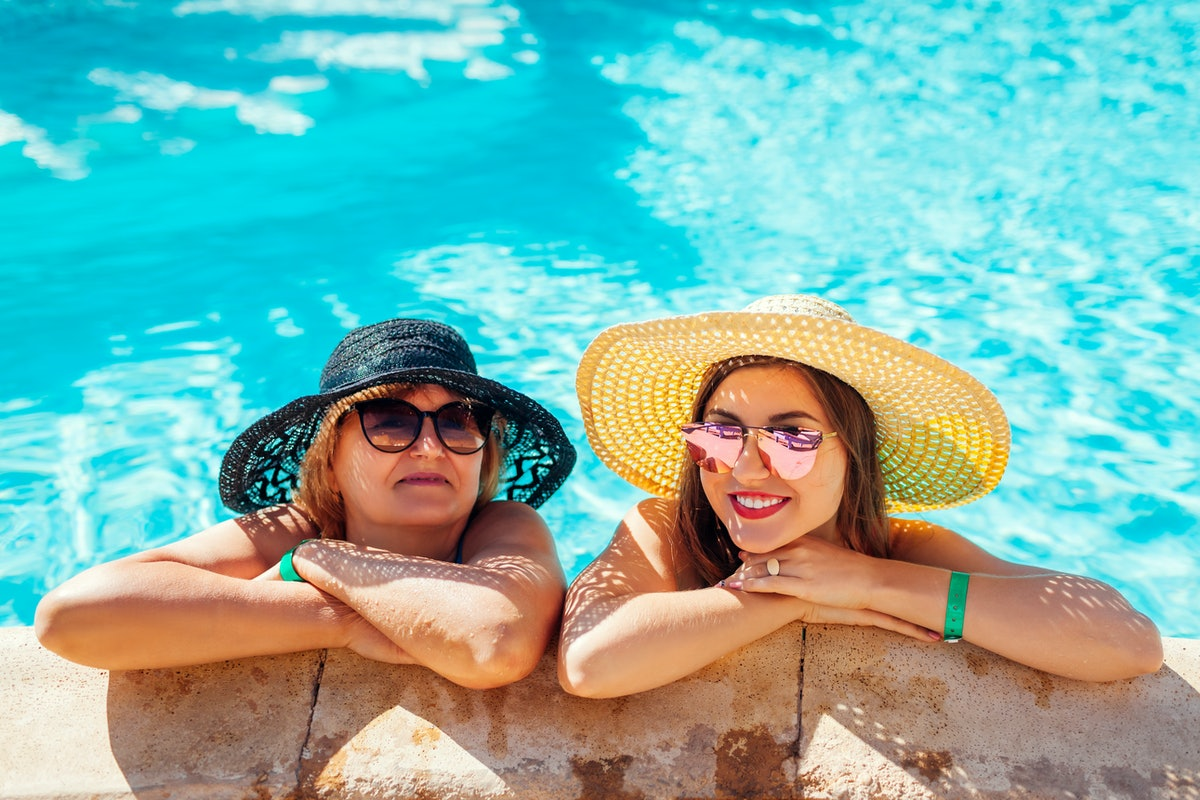 A mom and adult daughter smile and relax in a pool on a sunny day, while wearing sunglasses and sun hats.