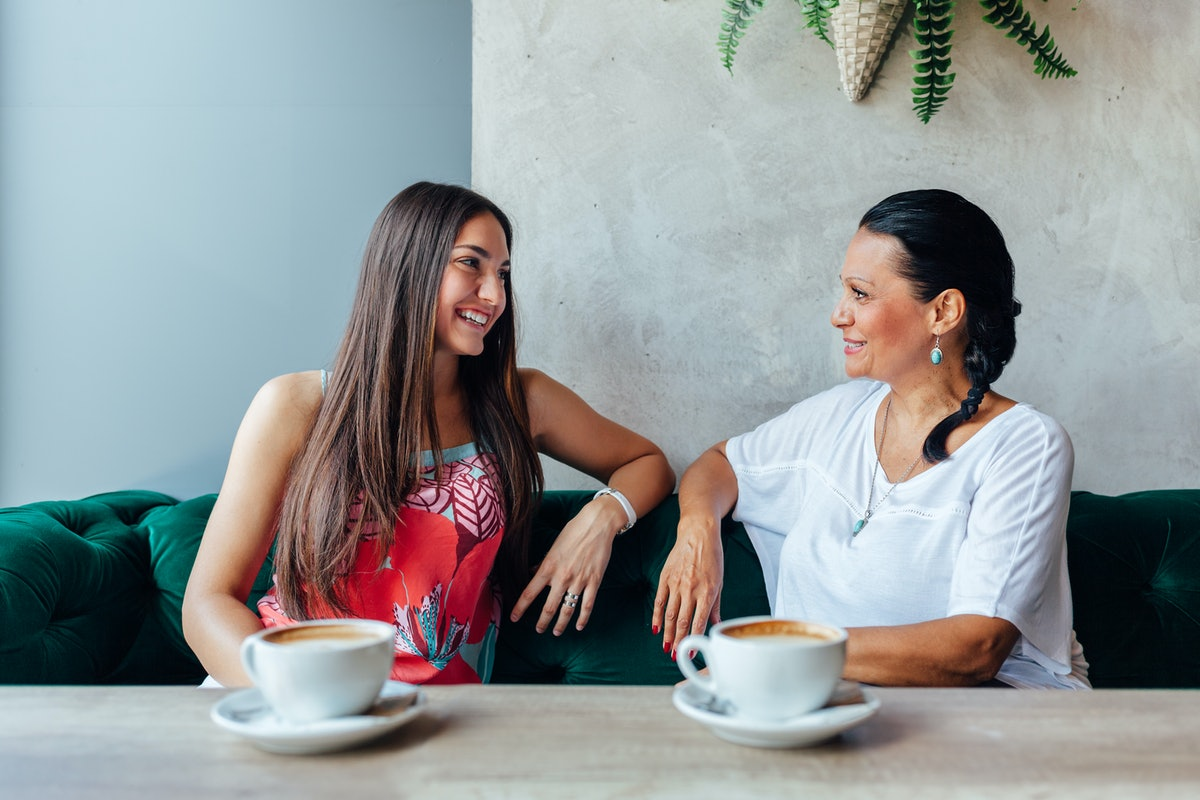 A mother and daughter laugh and chat in a booth of a café with cappuccinos in front of them.