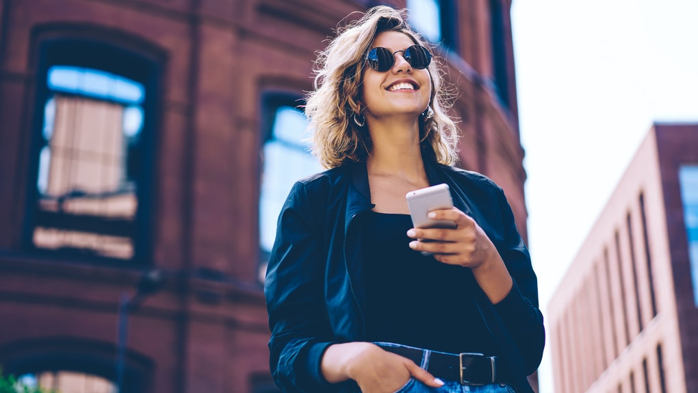 A happy woman, wearing sunglasses, stands with her phone in her hand outside.