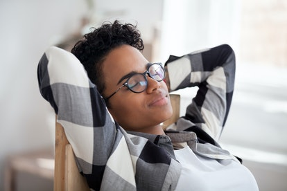 Relaxed calm happy black woman resting taking healthy break holding hands behind head breathing fresh air in office, tired african girl enjoying peaceful mood stress relief dreaming lounging concept