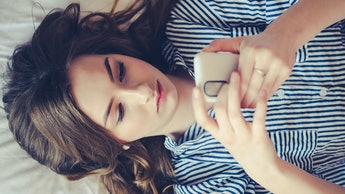 Closeup of sad teenage girl lying in bed using her mobile. Young pretty woman with bored expression ...