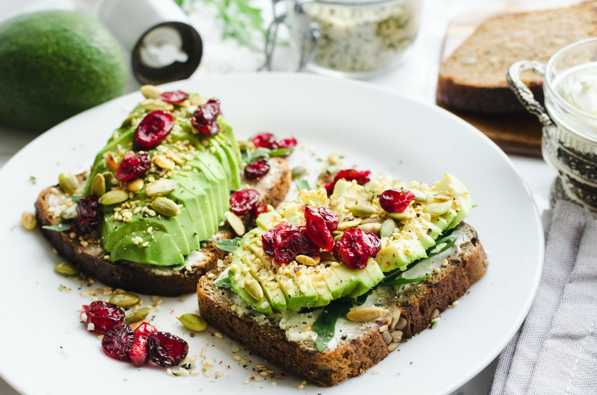 A plate of colorful avocado toast with cranberries on top sits on the table.