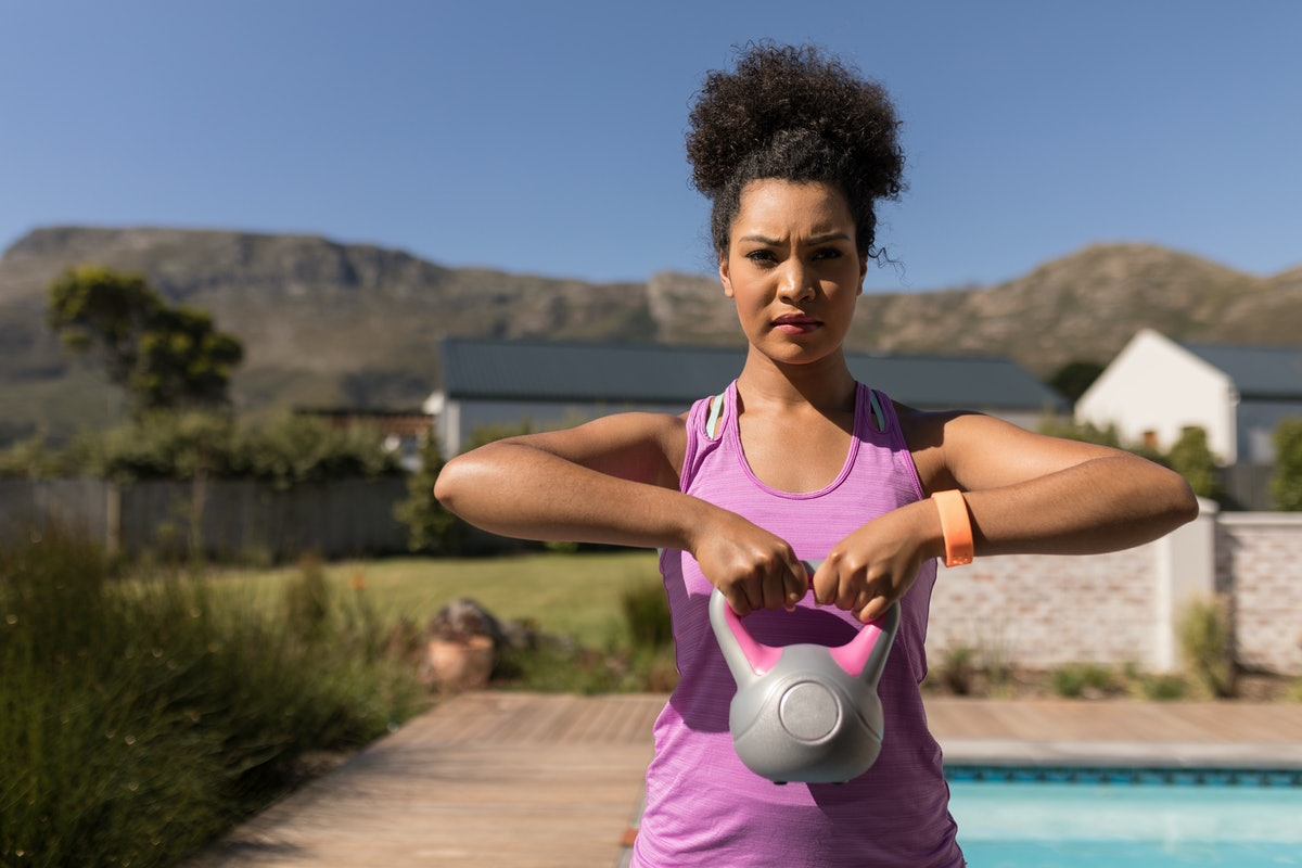 Front view of a young African American woman exercising with kettlebell in front of the swimming poo...