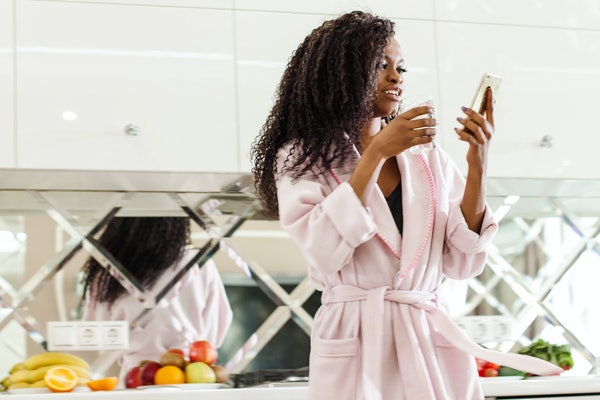 A woman in her pink robe stands in her kitchen, holding her phone and a glass of water.