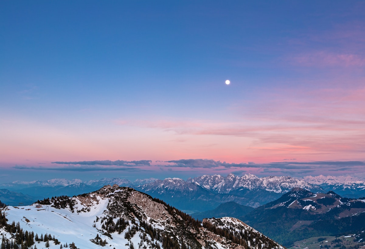 A full moon is above snow-capped mountains and a pink sky after sunset.