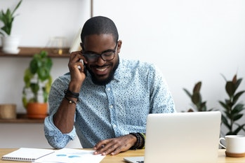 Handsome african manager sitting at office desk in front of laptop hold mobile phone make pleasant business or informal call. Successful businessman looking at financial statistic shown on documents
