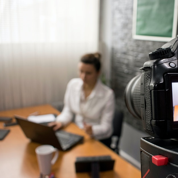 Video camera shoots a young businesswoman sitting at a table in front of a laptop