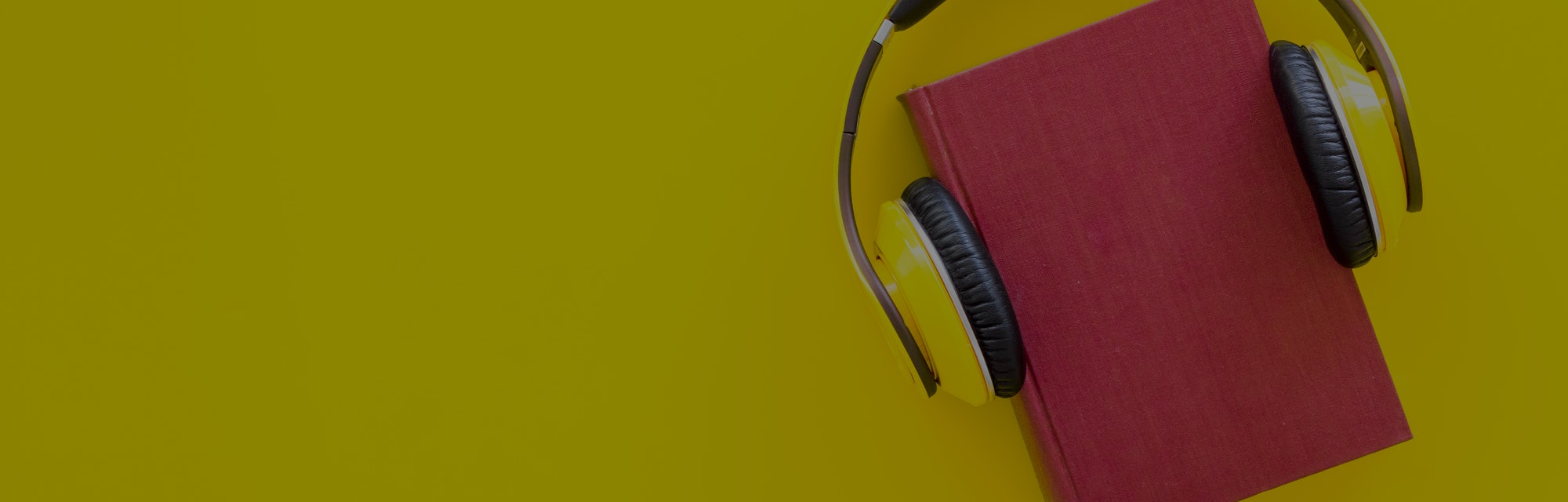 Audiobooks concept. Headphones put over hardback book with empty cover on yellow background top view copy space