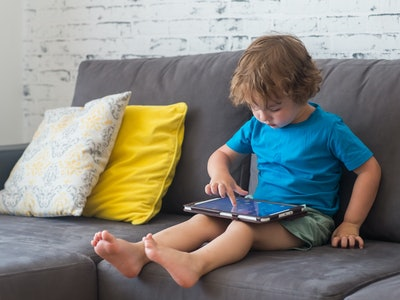 Little cute boy in a blue T-shirt playing games on a tablet and watching cartoons